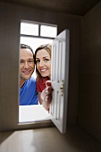 A young couple looking through the door of a model house