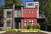 Modernes Haus mit Fronten in verschiedenen Farben und Materialien; davor ein frisch angelegter Blumengarten