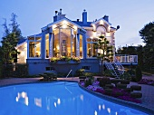 Grosses, verwinkeltes Haus mit Pool in der Abenddämmerung