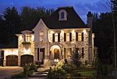 Außenansicht eines hell erleuchteten, imposanten Hauses in der Abenddämmerung