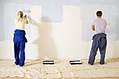 Junges Paar beim Streichen einer Wand