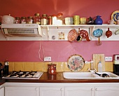 A gas hob, sink and a wall shelf in a kitchen