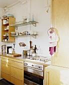 Einfache Küchenzeile mit Holzmöbeln und Gasherd mit Edelstahlfront