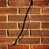 A cable hanging from a brick wall