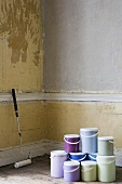 A paint roller and pots of paint in a room