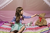 A girl playing with a teddy bear