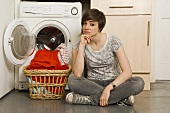 A young woman sitting in front of a washing machine