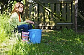 Ein Mädchen sitzt auf einer Mauer in einem Garten