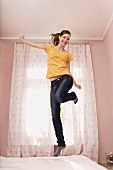 A teenage girl jumping on her bed