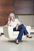 Porträt von Frau mittleren Alters sitzt auf modernem Sessel