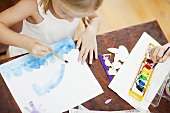 A girl painting with watercolours
