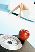 A red apple on bathroom scales (symbolising diet)
