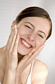 Smiling young woman with her hands on her cheeks