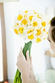 Woman holding white narcissi in her hands