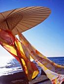 Sonnenschirm mit bunten Tüchern am Meer