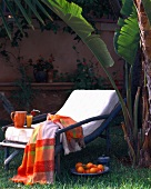 Deckchair with juice and oranges under palms
