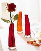 Eine rote Rose in roter Glasvase