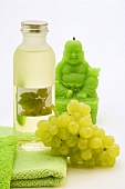 White grape seed oil, grapes and green Buddha candle