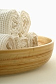 Rolled white towels in a wooden bowl