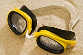 Yellow swimming goggles in sand