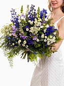Woman holding bouquet of flowers (with delphiniums)