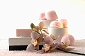 Soap in soap dish and cotton wool balls with orchid