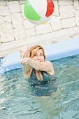 Blond woman playing with beach ball in swimming pool