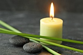 A candle, pebbles and papryus sedge