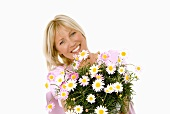 Cheerful woman holding bouquet of marguerites in her hands