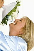 Smiling woman smelling bouquet of white roses