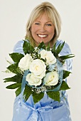 Smiling woman showing bouquet of white roses