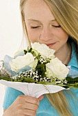 Young girl smelling bouquet of white roses