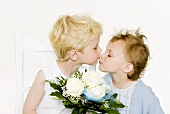 Two children kissing over a bouquet of white roses