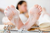 Feet of woman lying in bathtub