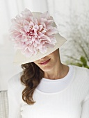 Woman in hat decorated with large flower