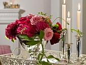 Red flower arrangement in silver bowl, candles beside it