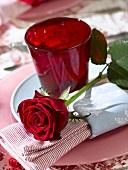 Gedeck mit rotem Glas und roter Rose
