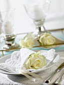 Place-setting with white rose wrapped in napkin