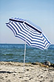 Blue and white beach umbrella by the sea