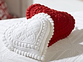 Two small heart-shaped cushions (red and white)
