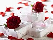 Weiss verpackte Geschenke mit roten Rosen