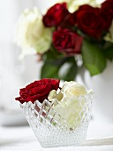 Red and white roses in a crystal glass