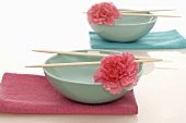 Asian bowls with chopsticks and flowers