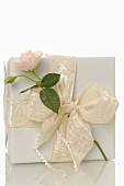 Gift in white wrapping paper with rose