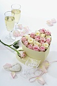 Roses in heart-shaped box & two glasses of sparkling wine