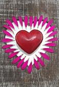 Herz im herzförmigen Holzbrettloch mit Blütenblättern