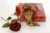 Gift, red rose and glass of sparkling wine