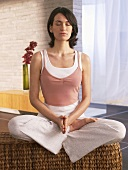 Woman sitting cross-legged practising yoga