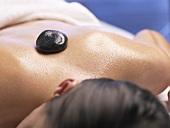 Woman having a warm stone massage