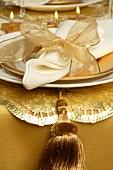 Weihnachtsgedeck mit weisser Serviette und goldener Schleife